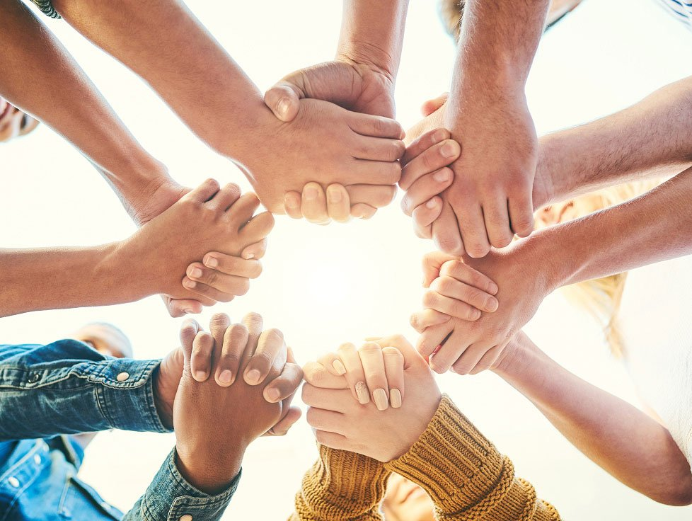 group of people holding hands, light shining brightly